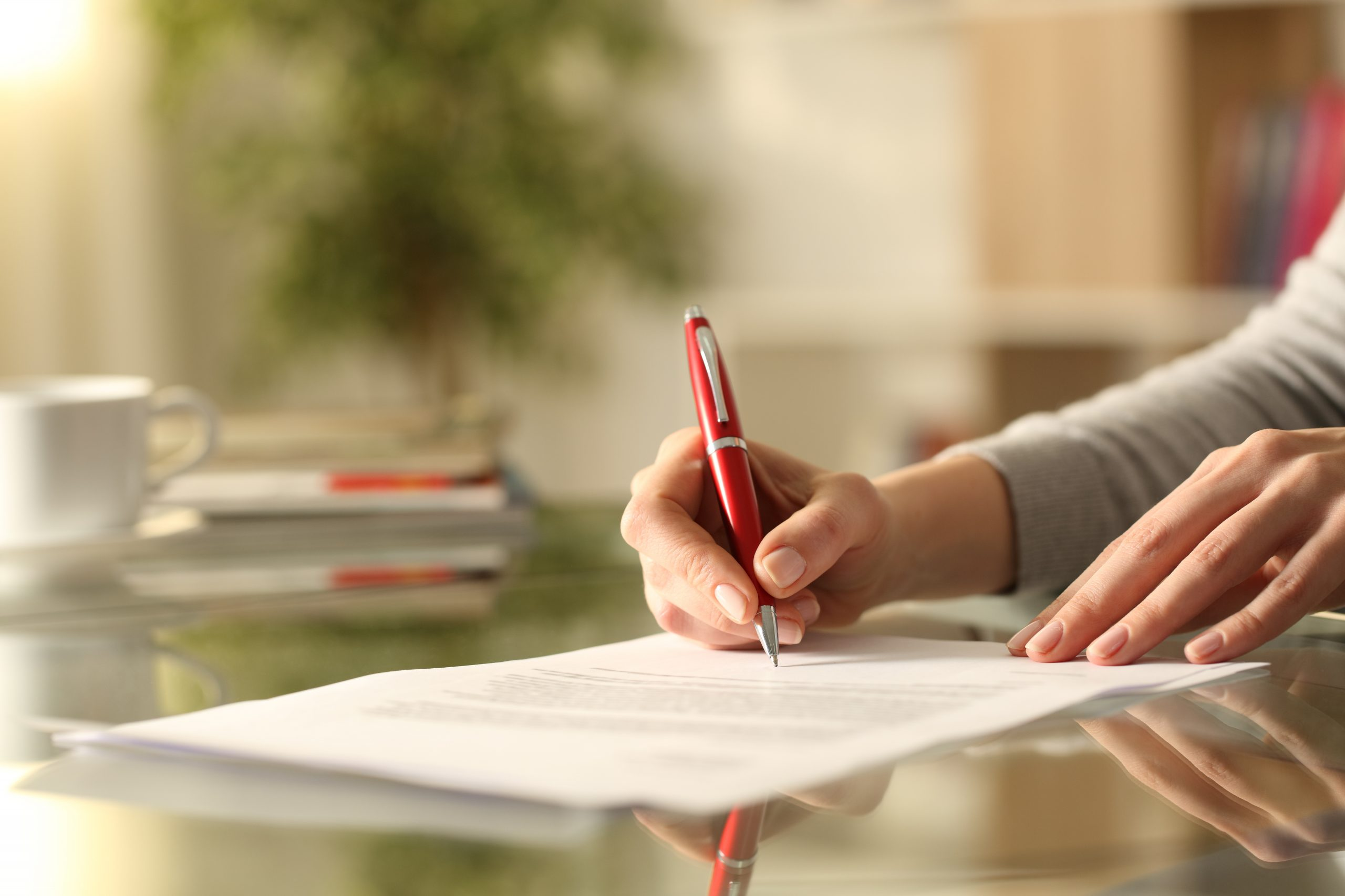 Woman signing document with pen on a desk at home