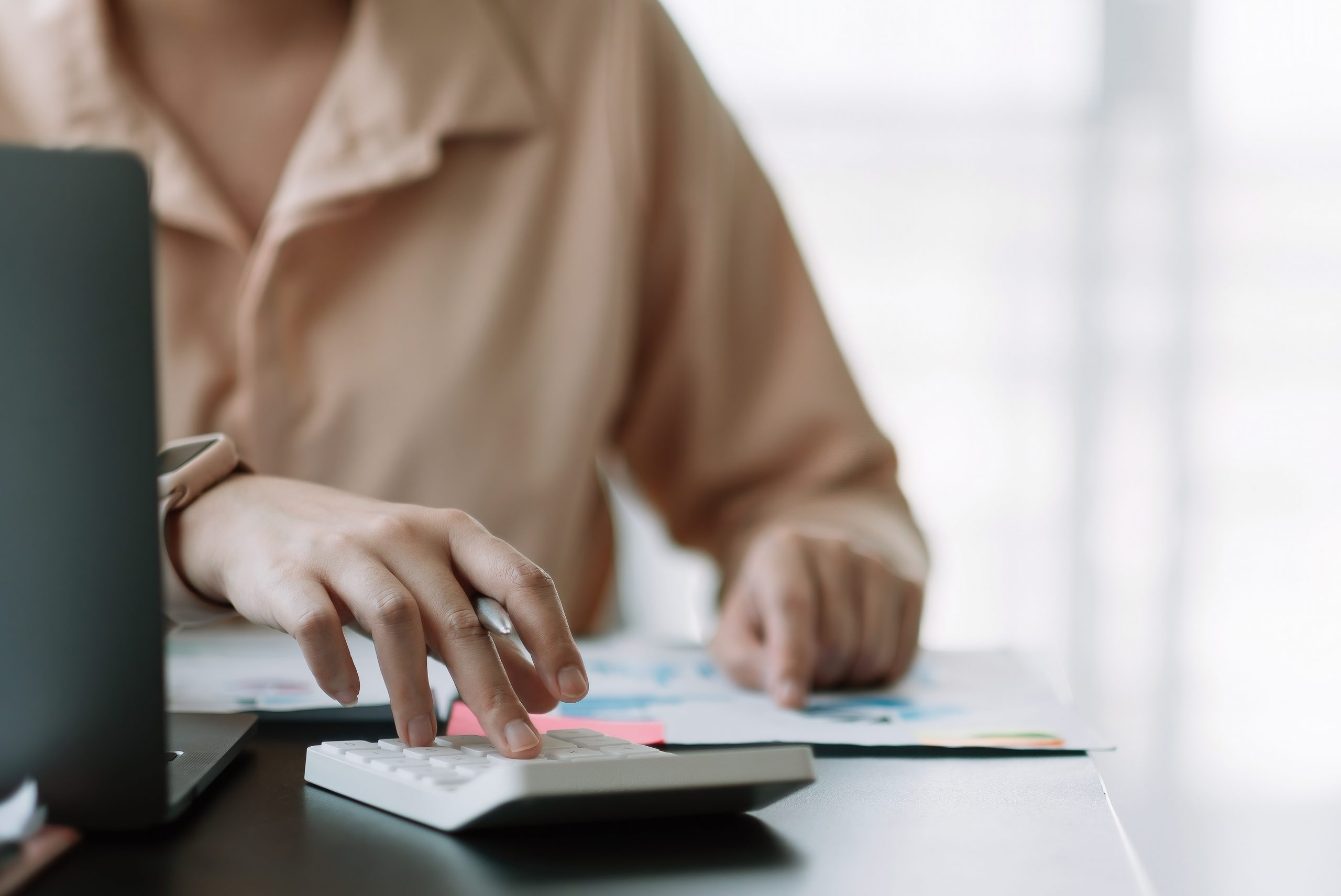 Business woman using calculator for do math finance on wooden desk in office, tax, accounting, statistics home accounring concept.